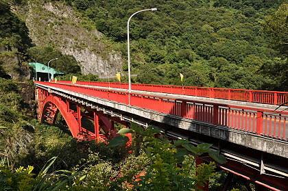 ,途中经过一座钢构红色的拱桥,跨越浊水溪,桥旁的山岭峭拔,桥