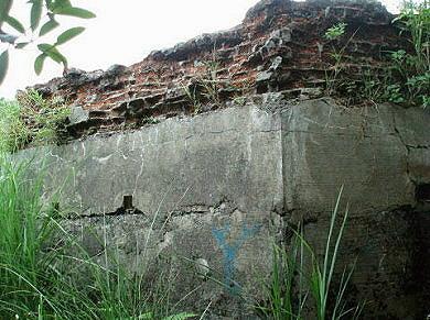 围墙上层采砌砖,下层混凝土结构.墙面有射口.